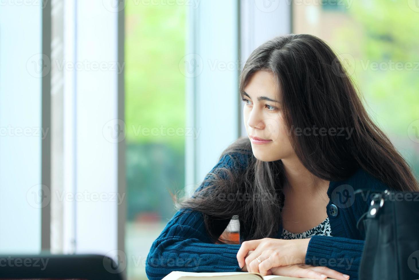 giovane studente guardando fuori dalla finestra mentre studiava foto