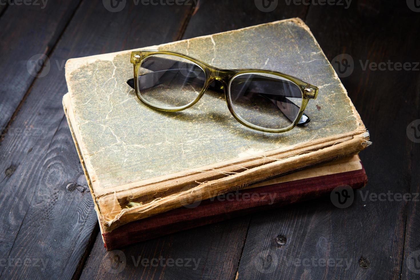 occhiali da lettura vintage sulla pila di libri foto