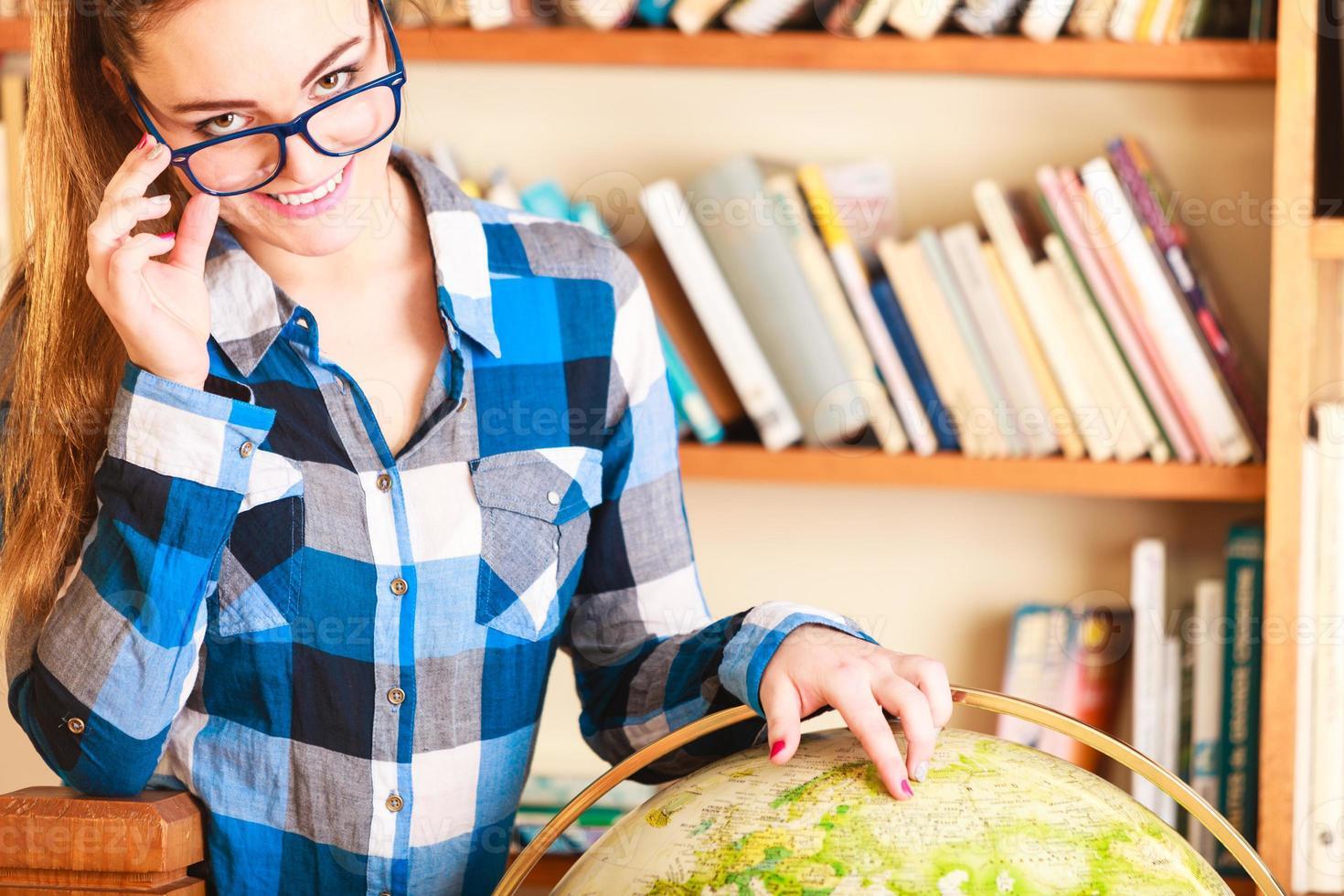 ragazza in biblioteca che punta al globo foto