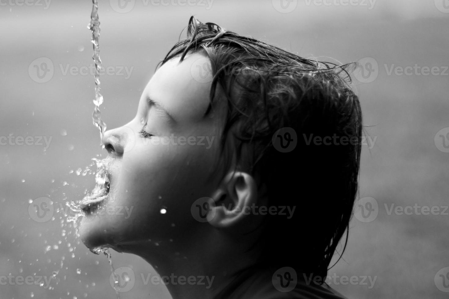 gocce d'acqua schizzarono sul viso del ragazzo foto