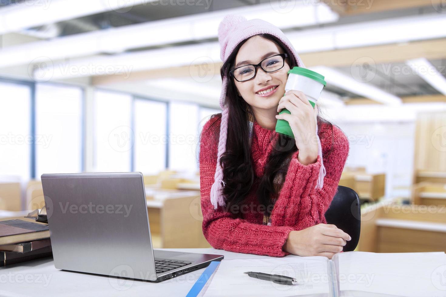 bella ragazza con maglione che studia in classe foto