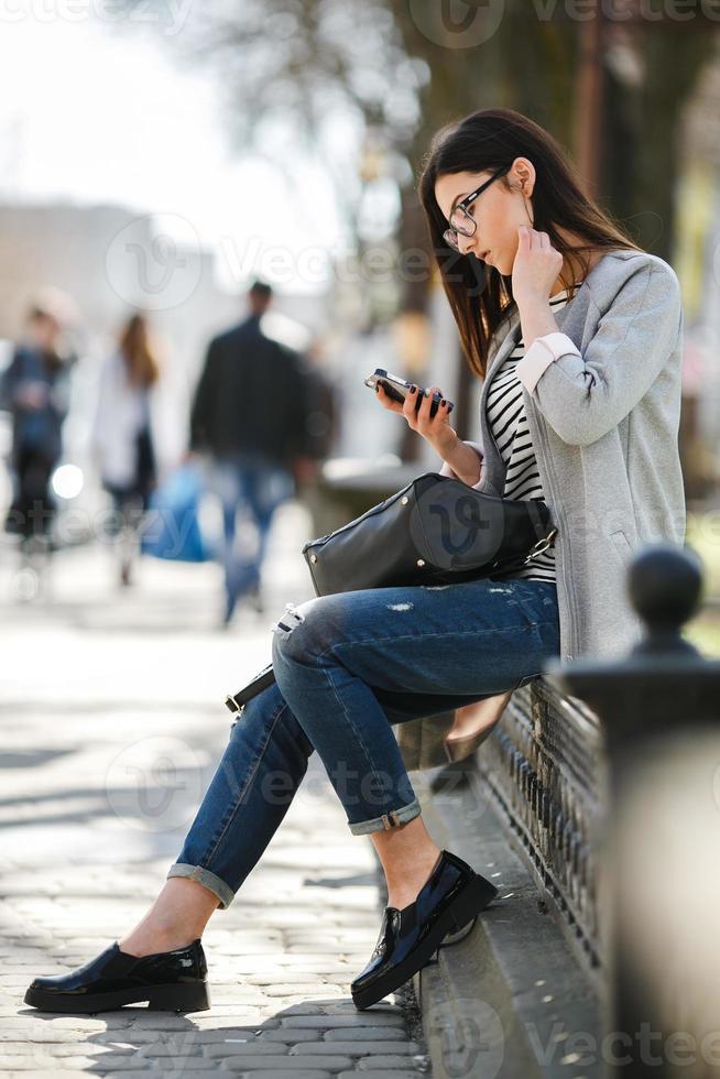 modella nel mezzo della città con il telefono foto