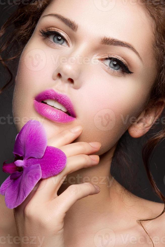 Ritratto del primo piano di bella donna con trucco luminoso foto