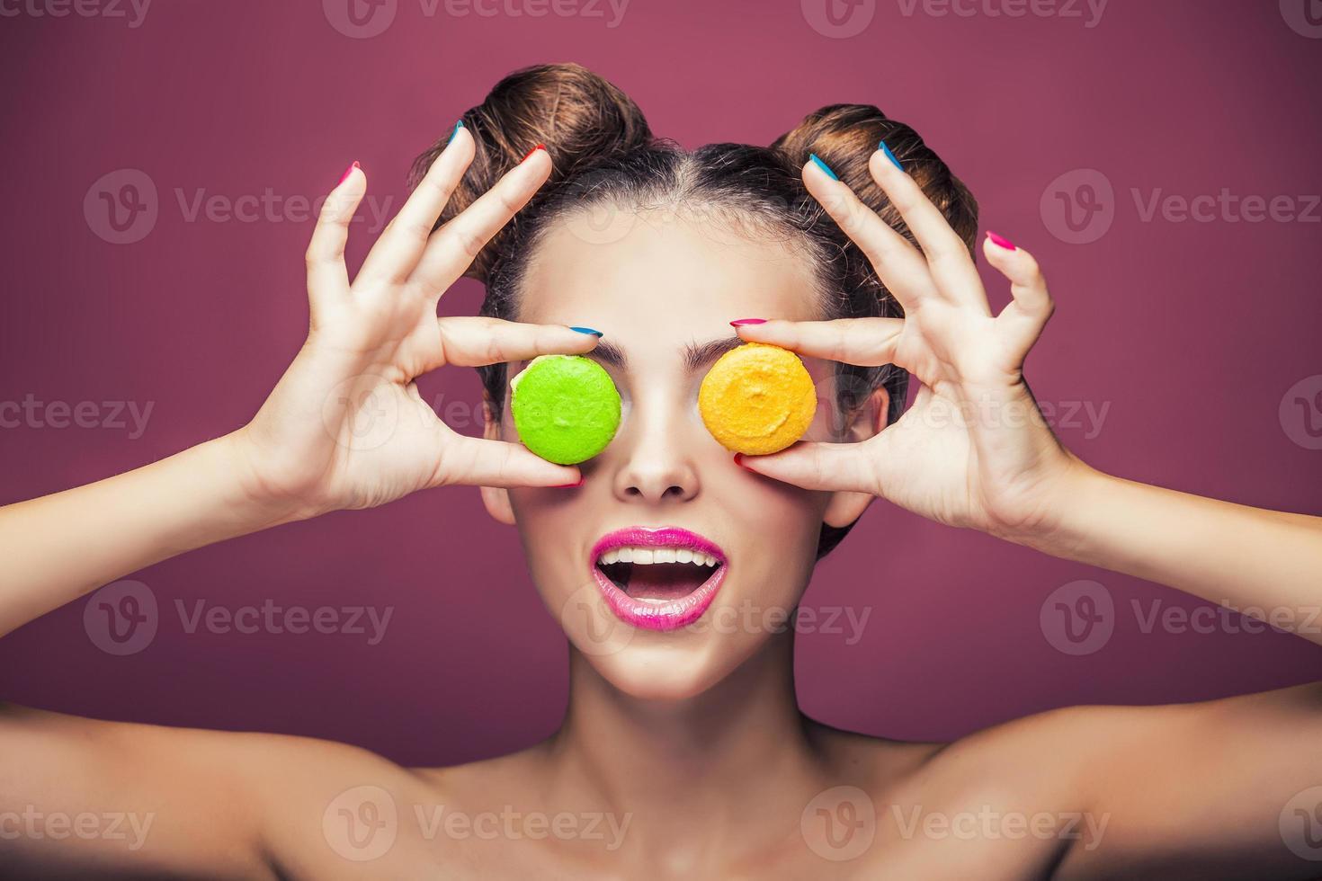 modella, una donna con trucco luminoso e biscotti colorati scherzando. foto