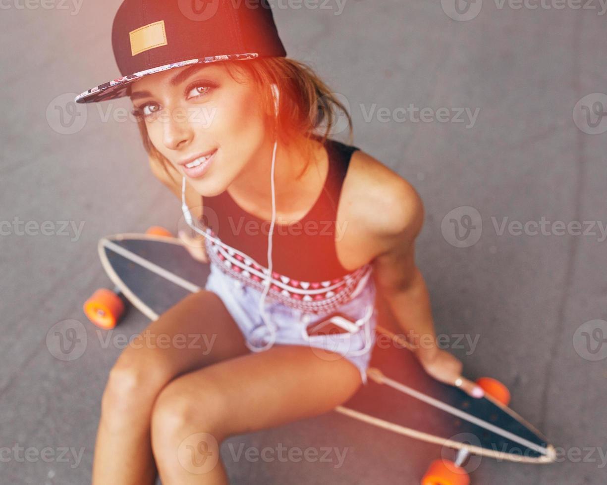 stile di vita di moda, bella giovane donna con longboard foto