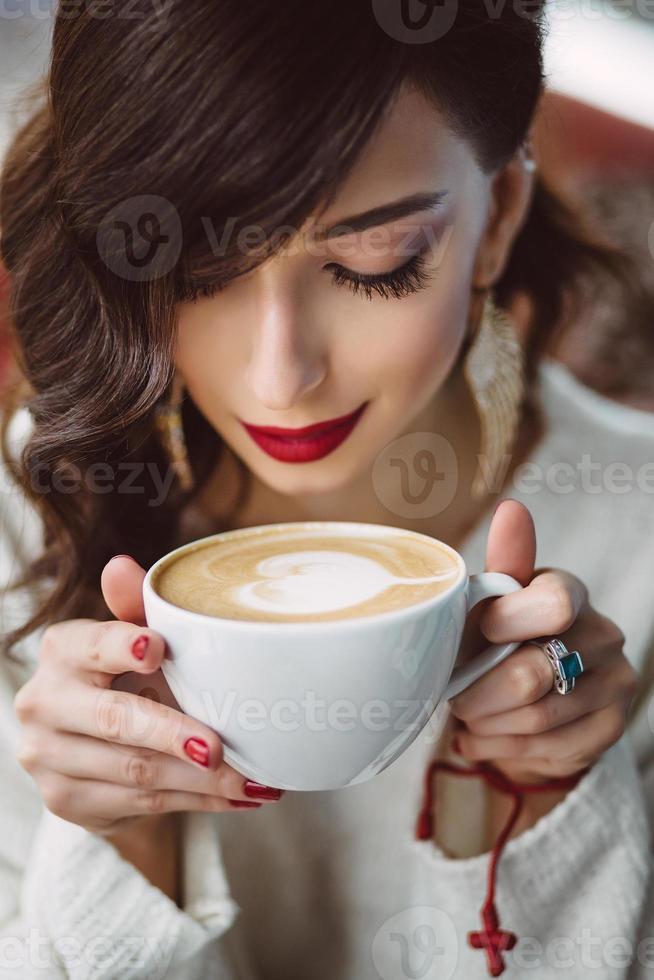 ragazza che beve caffè in un caffè alla moda foto