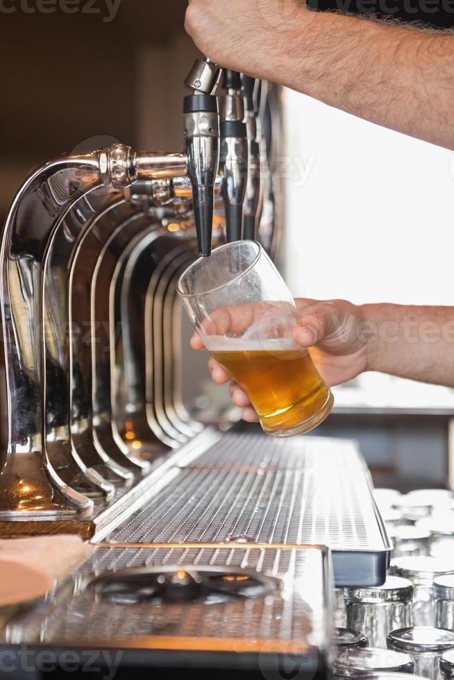 barista tirando una pinta di birra foto