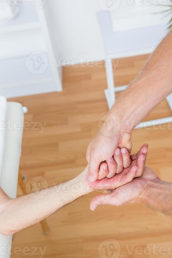 Fisioterapista che fa massaggio alle mani foto