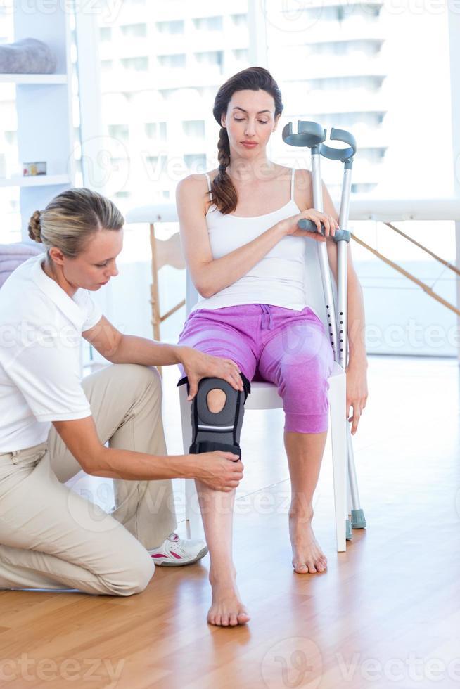 medico che esamina il ginocchio dei suoi pazienti foto