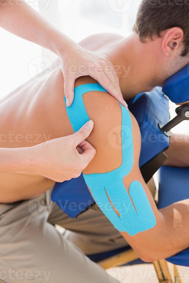 medico che esamina la sua spalla paziente foto