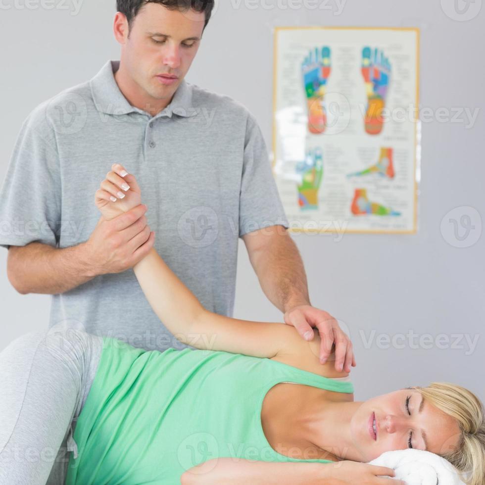 bel fisioterapista che tratta il braccio dei pazienti foto