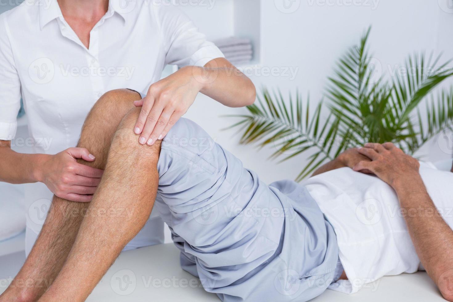 uomo con massaggio al ginocchio foto