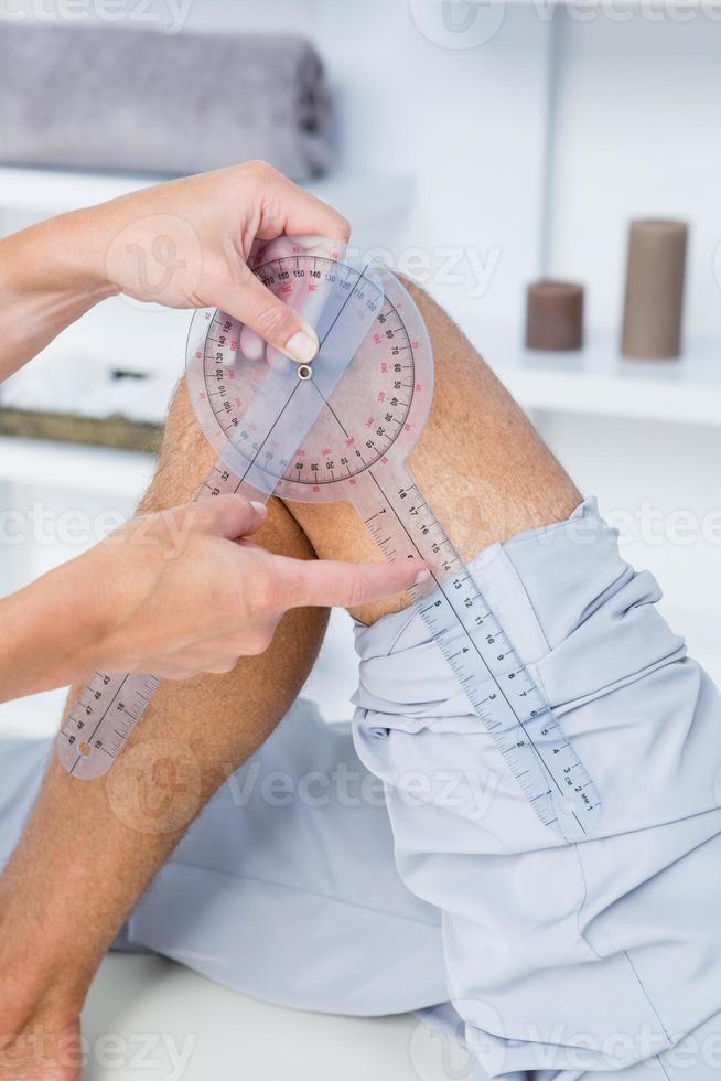 medico che esamina la gamba dell'uomo con lo strumento foto