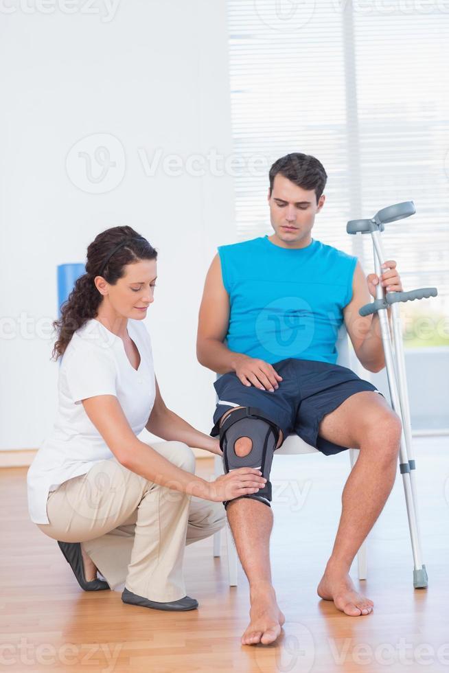 medico che esamina il suo ginocchio paziente foto
