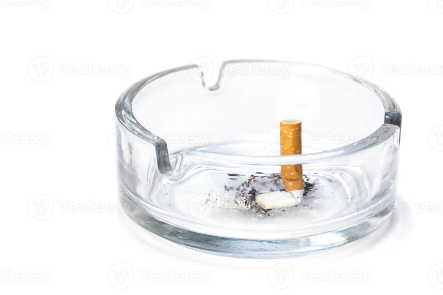 mozzicone di sigaretta in un portacenere, isolato su bianco foto