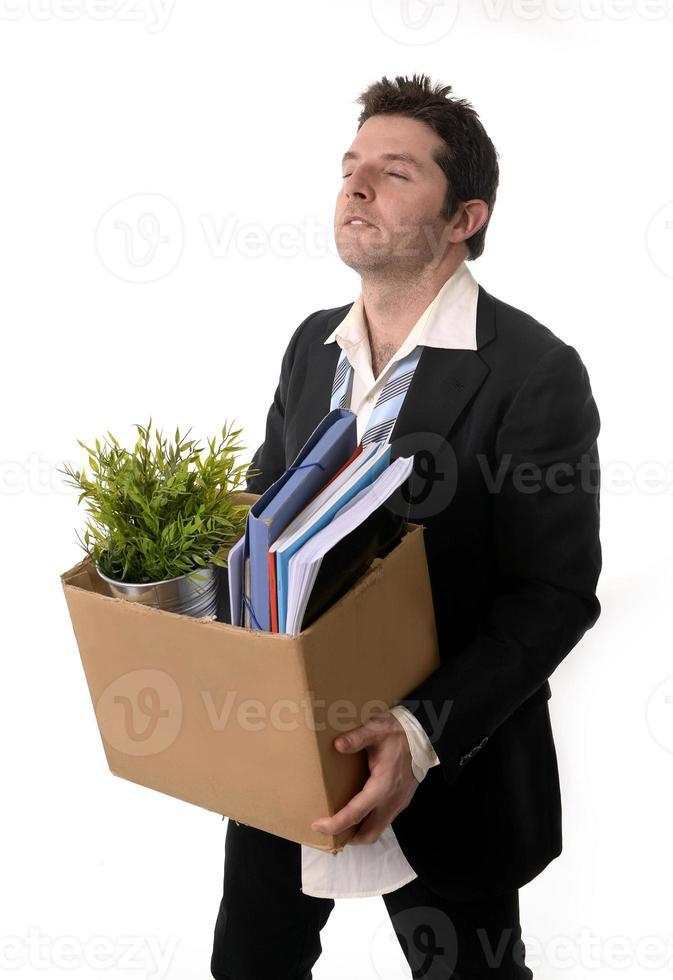 uomo d'affari disordinato con scatola di cartone licenziato dal lavoro foto