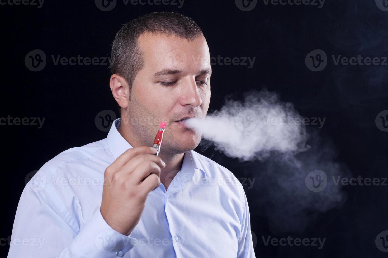gli uomini fumano una sigaretta elettronica foto