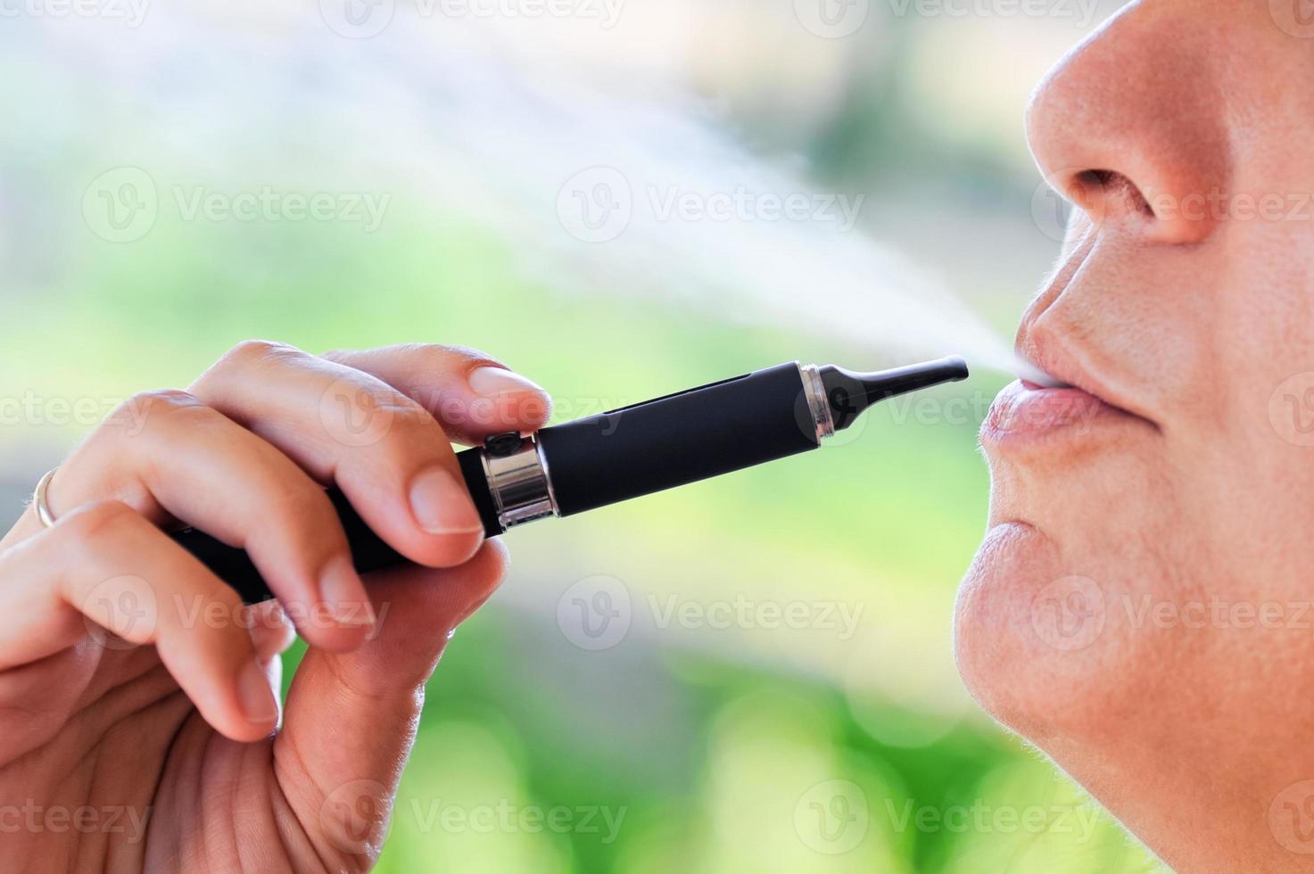 fumatore di sigaretta elettronica con vapore foto