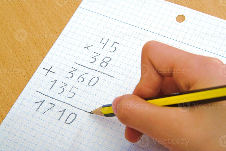 bambino facendo una moltiplicazione matematica a scuola foto