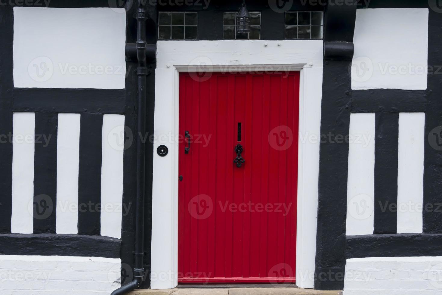 porta d'ingresso rossa in una casa tudor con cornice in legno foto