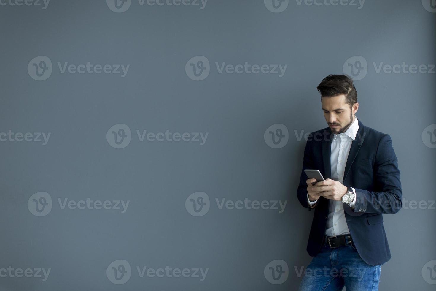giovane con il cellulare in ufficio foto
