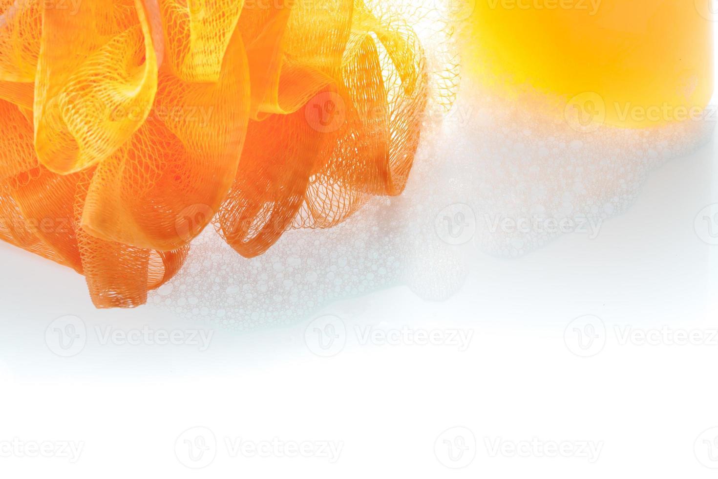 scrub in fibra arancione e gel doccia con bolla su bianco foto