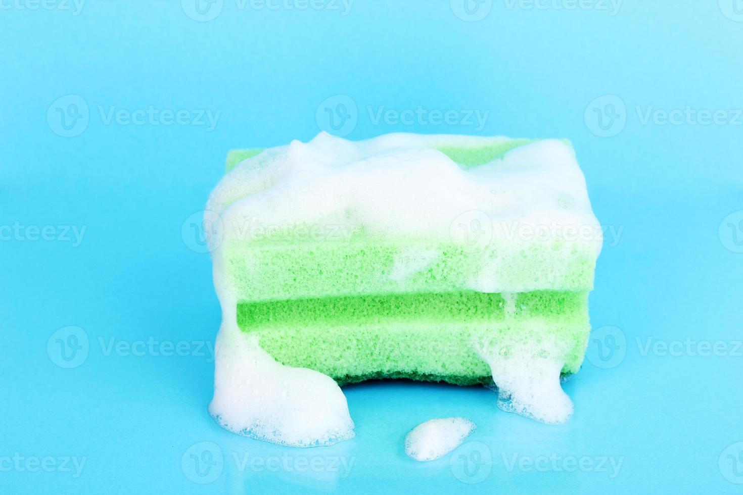 spugna con schiuma di detersivo per piatti su sfondo blu foto