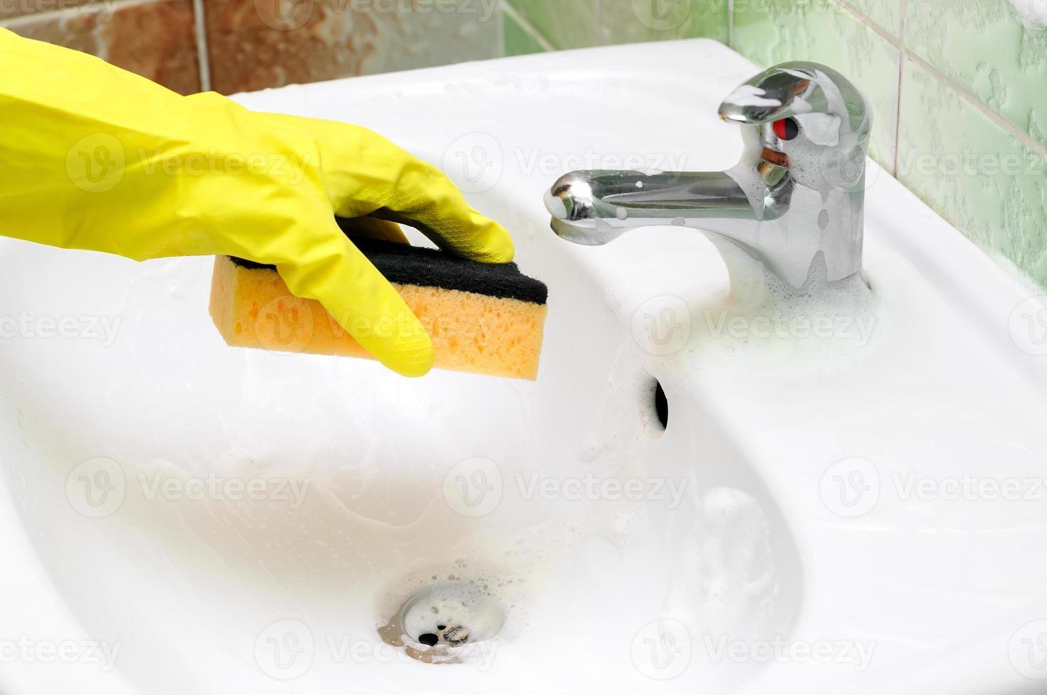 pulizia del rubinetto del lavandino del bagno foto