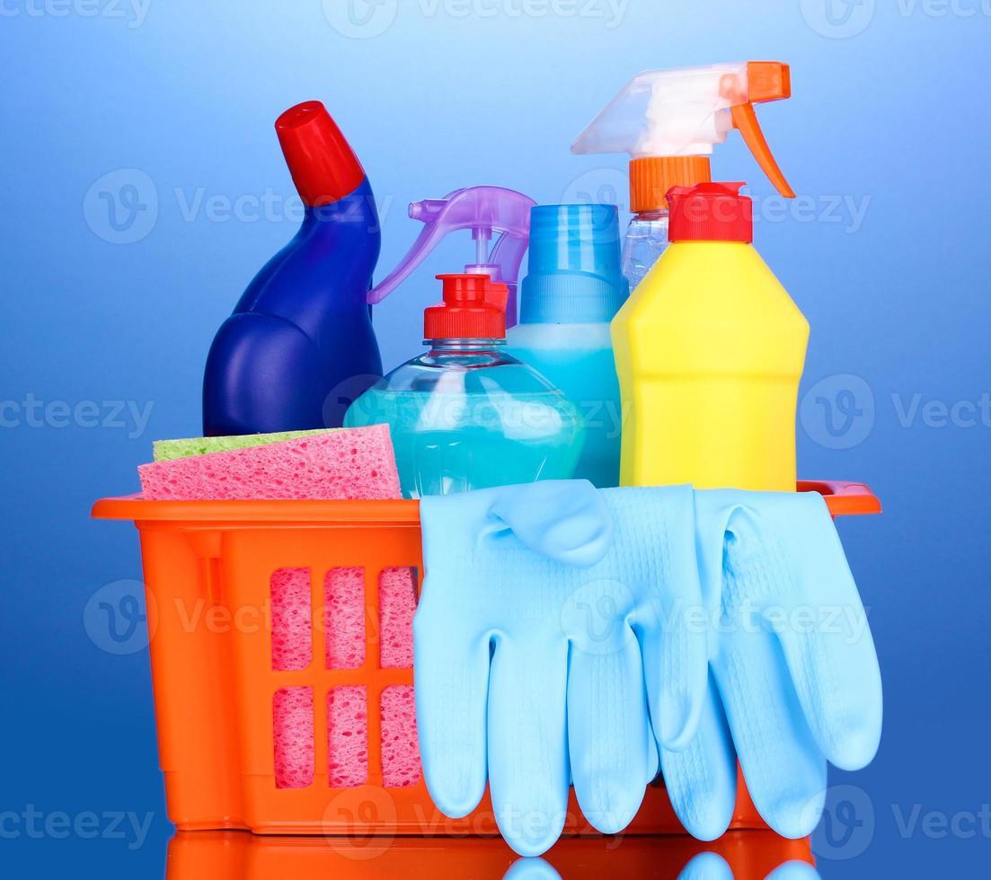 cesto con articoli per la pulizia su sfondo blu foto