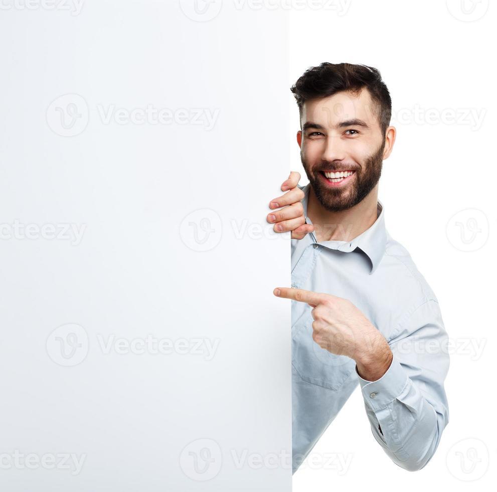 giovane uomo barbuto che mostra insegna in bianco, isolata sopra bianco foto
