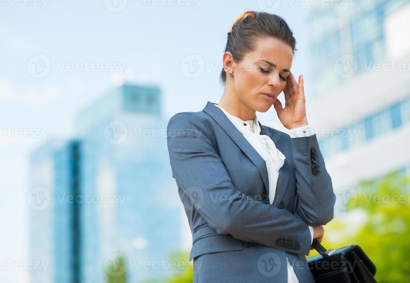 donna d'affari stressata con valigetta nel distretto di ufficio foto