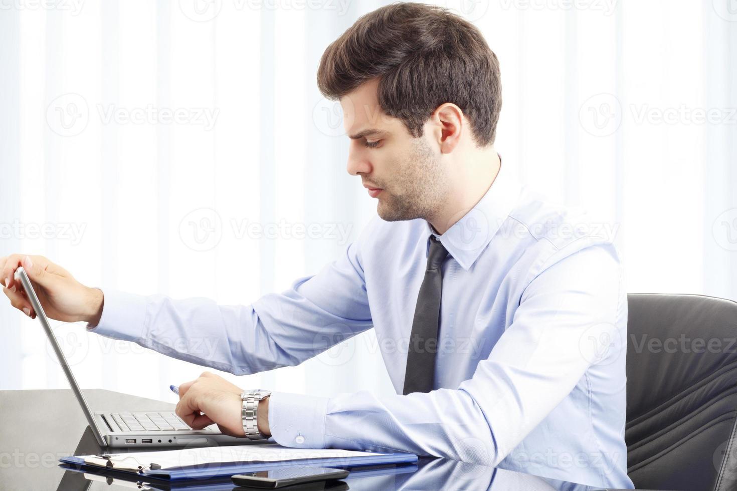 Ritratto di giovane uomo d'affari con il portatile foto
