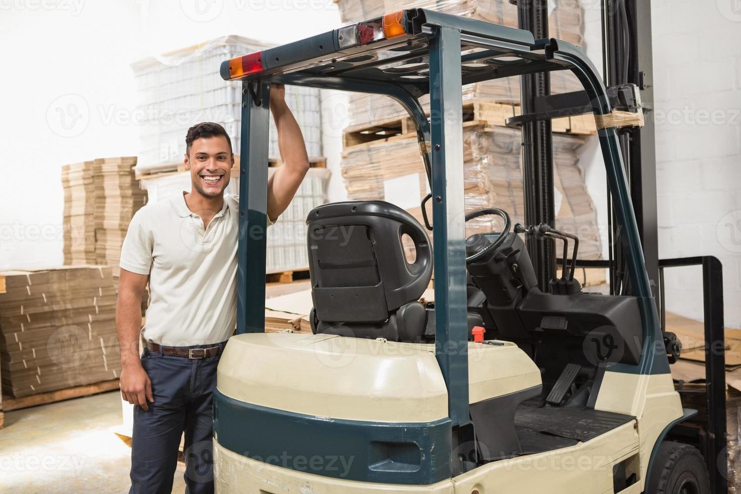 lavoratore manuale appoggiato al carrello elevatore foto