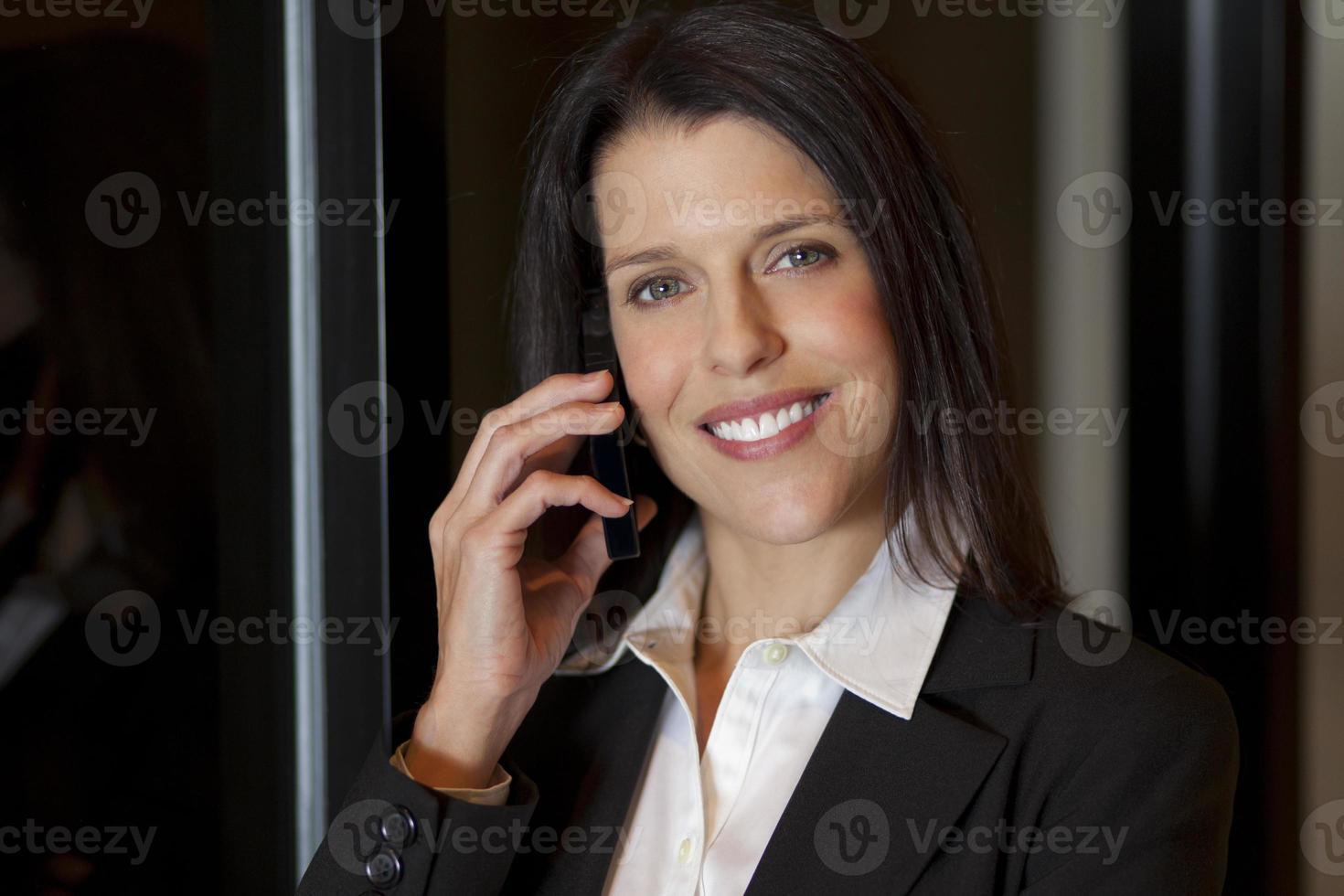 bella imprenditrice sorridente parlando su un cellulare foto