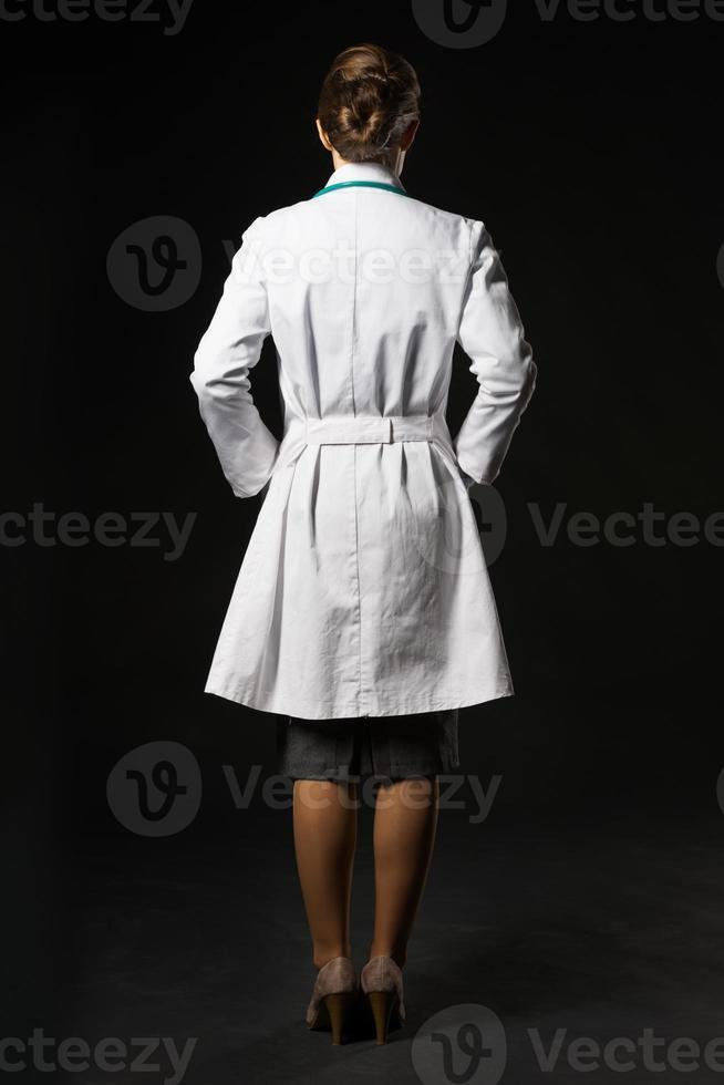ritratto integrale della donna del medico isolata sul nero foto