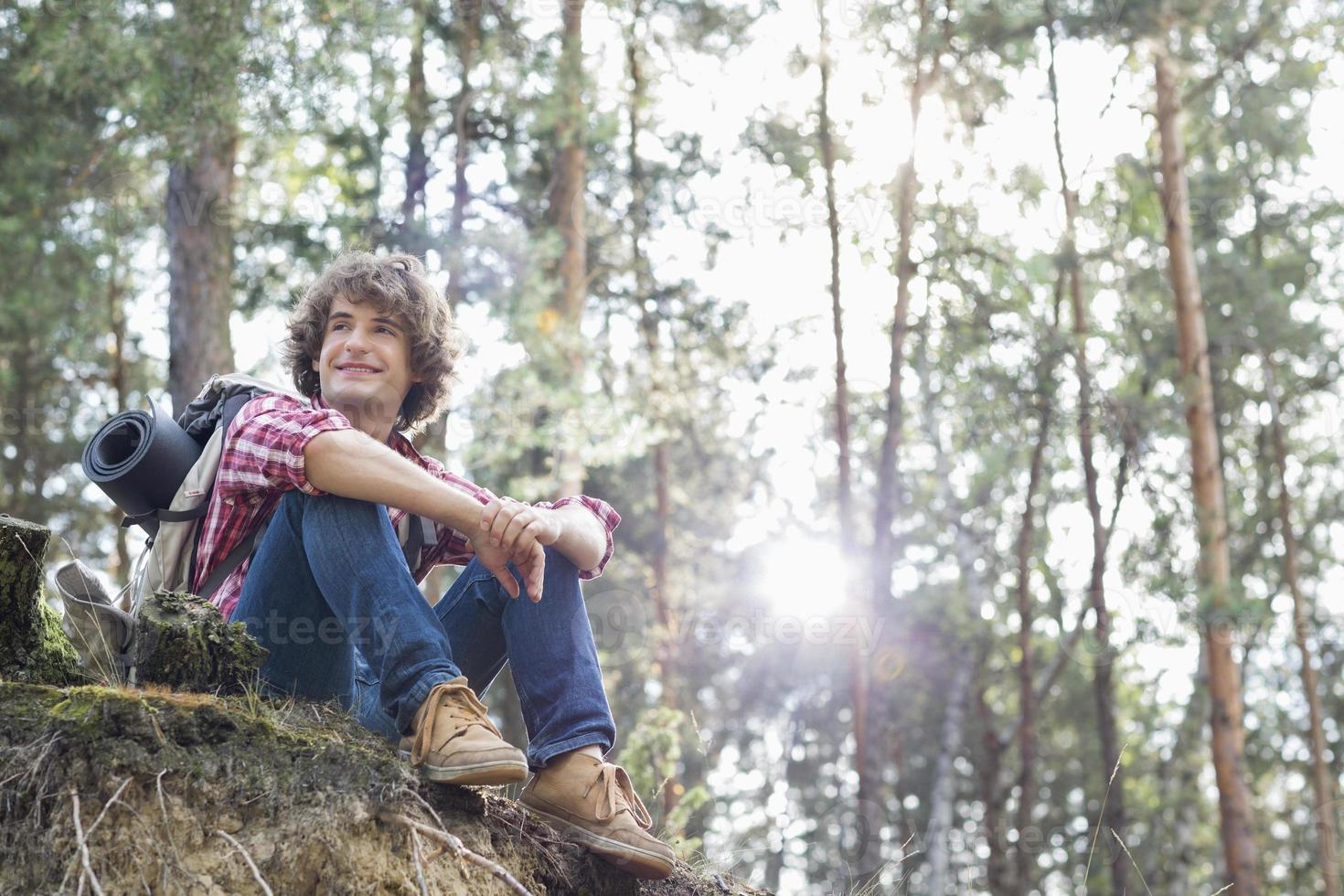 Viandante maschio sorridente che distoglie lo sguardo mentre sedendosi sulla scogliera foto