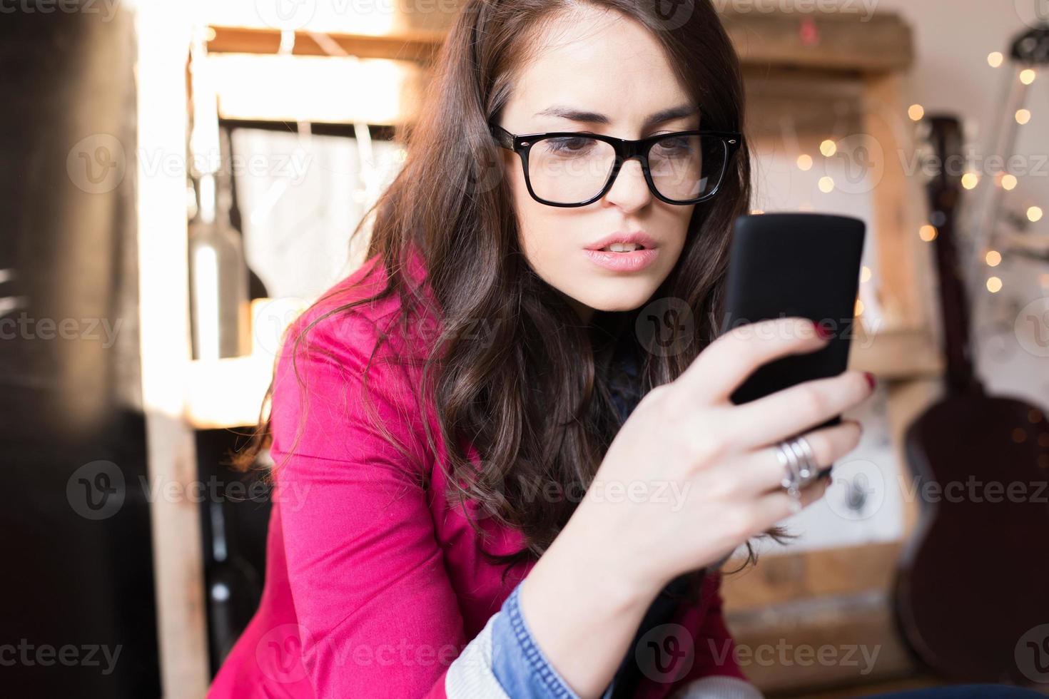 donna giovane bella hipster utilizzando smart phone in ufficio foto