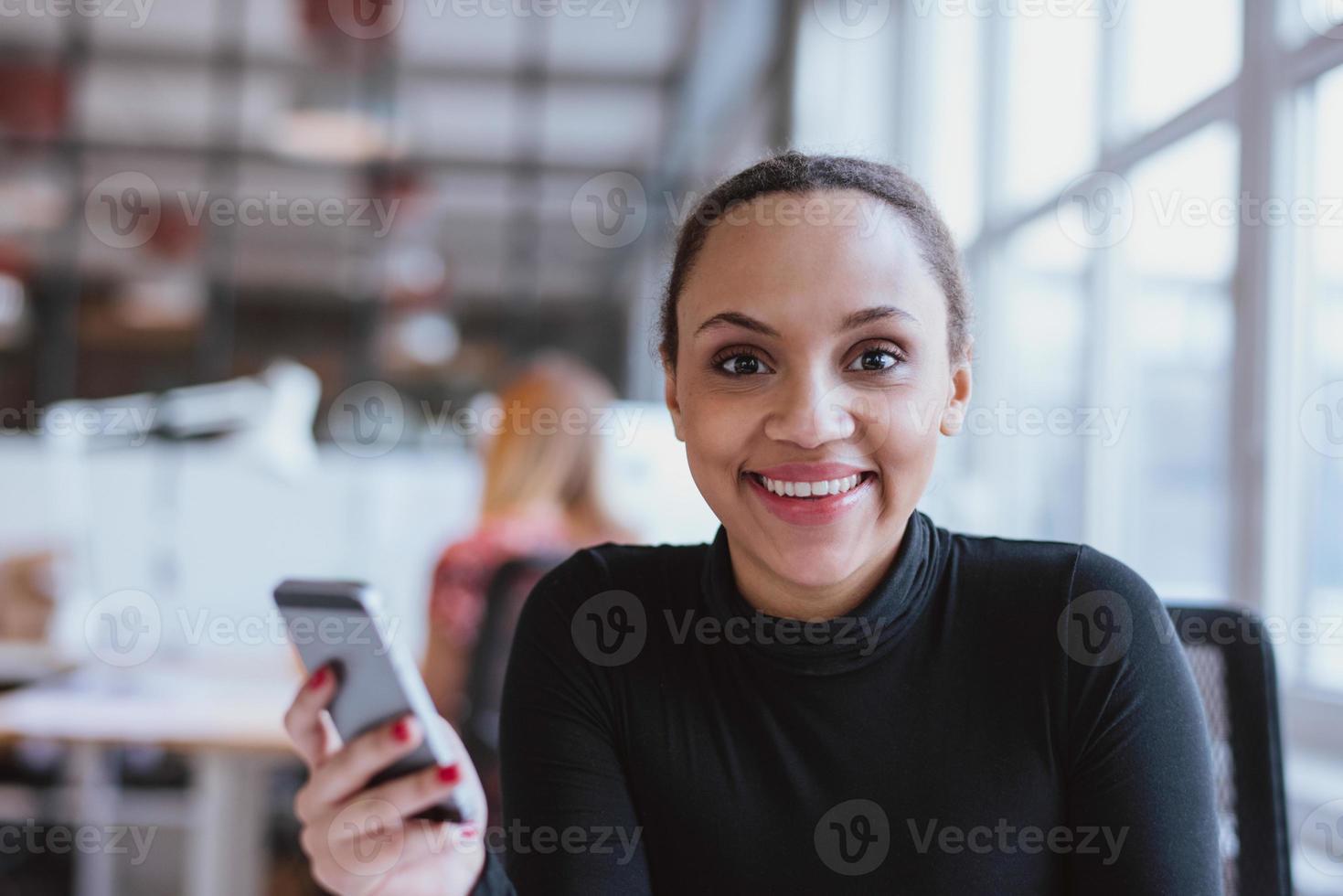 donna africana al lavoro guardando sorridente della fotocamera foto