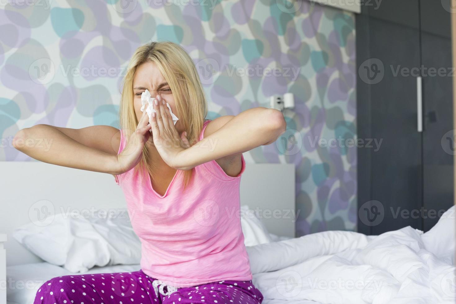 giovane donna che soffia il naso in carta velina foto