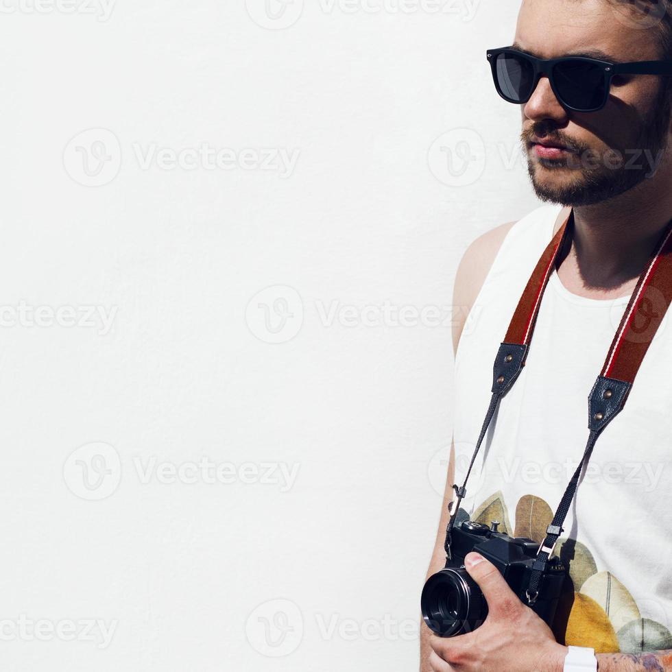 primo piano di uomo giovane hipster con fotocamera all'aperto. foto