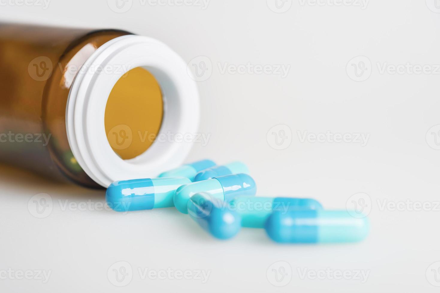 vengono versate le capsule di medicina e bottiglia blu foto
