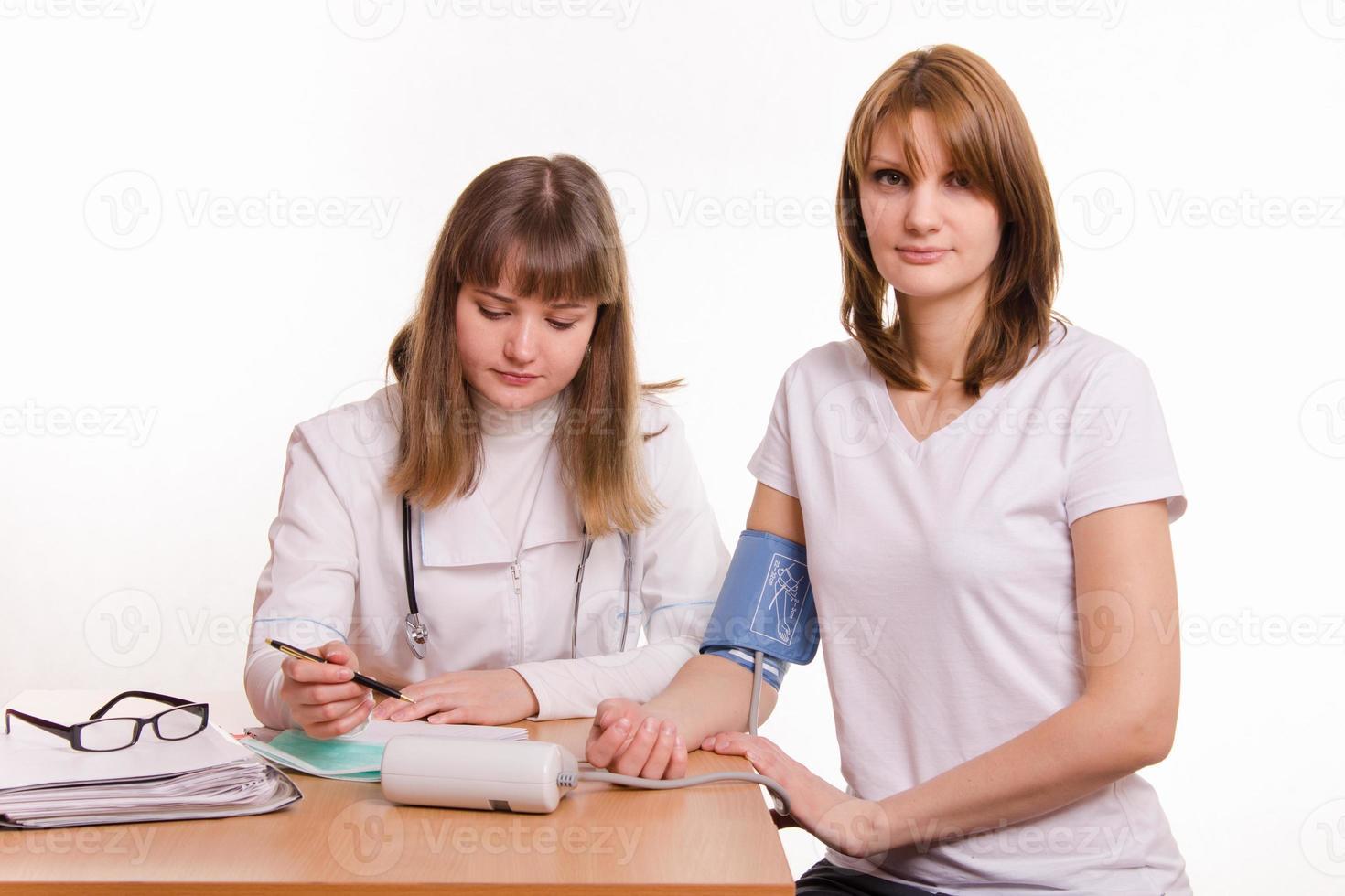 il medico scrive le letture del tonometro nella scheda paziente foto