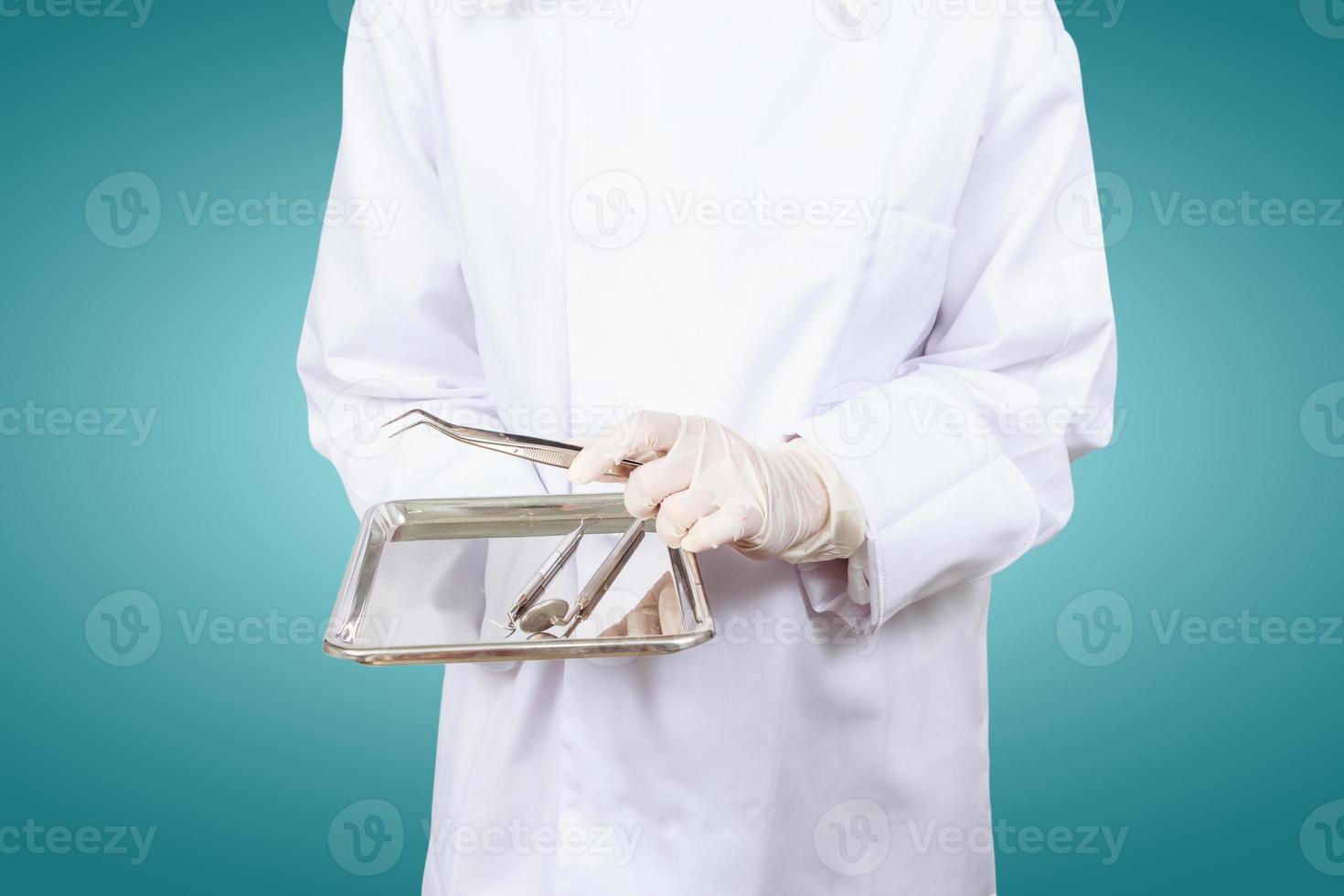 mano del dentista o degli assistenti dentali. tenere strumenti per dentisti. foto