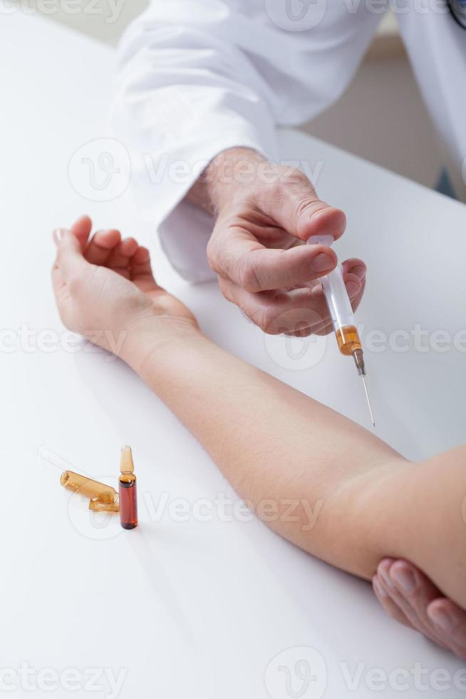 la mano dell'infermiera che fa un'iniezione foto