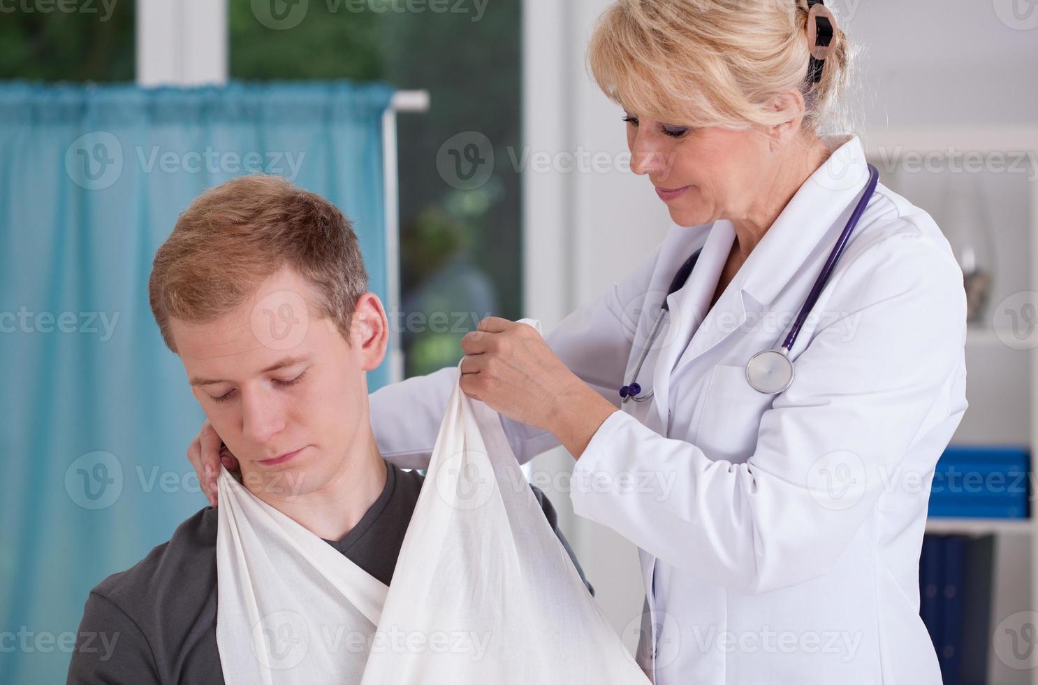 medico che mette l'imbragatura al paziente foto