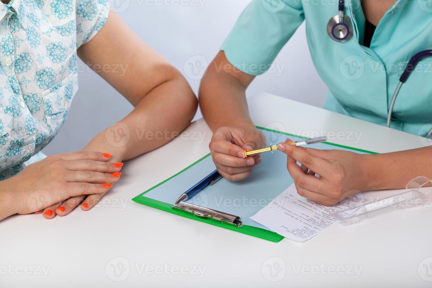 medico che mostra al paziente una siringa foto