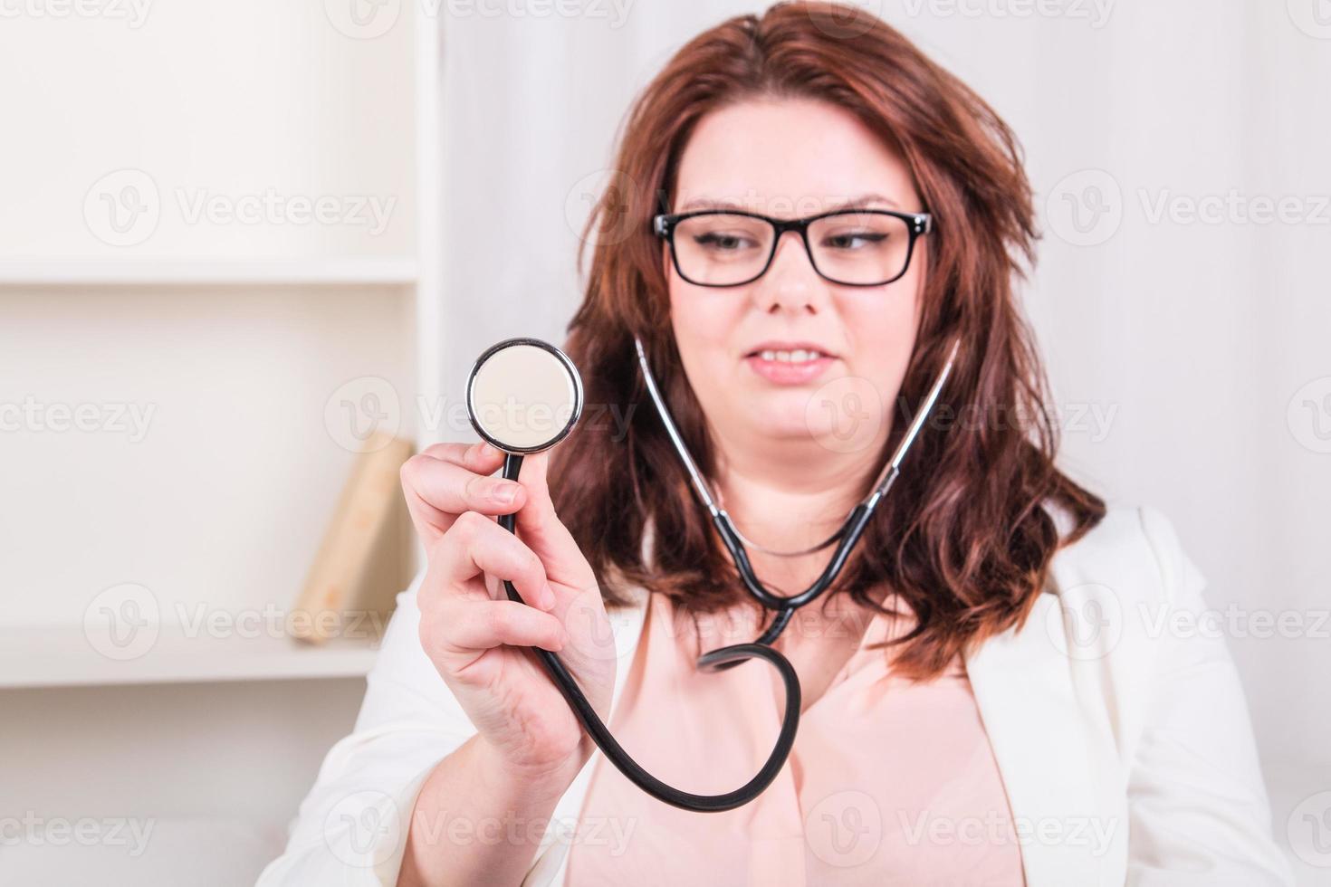 esaminare la giovane dottoressa con uno stetoscopio foto