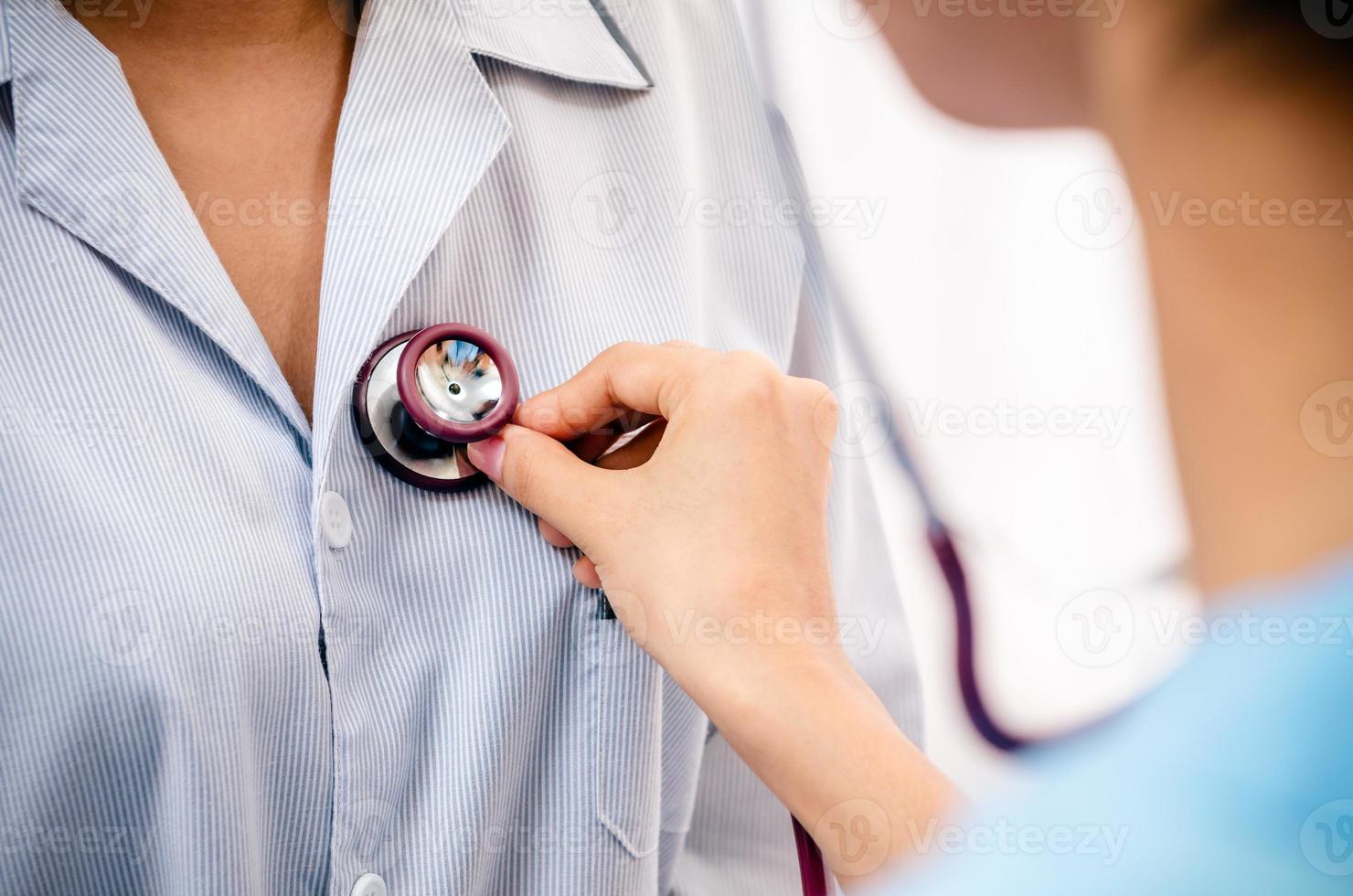 medico che ascolta il cuore del paziente foto