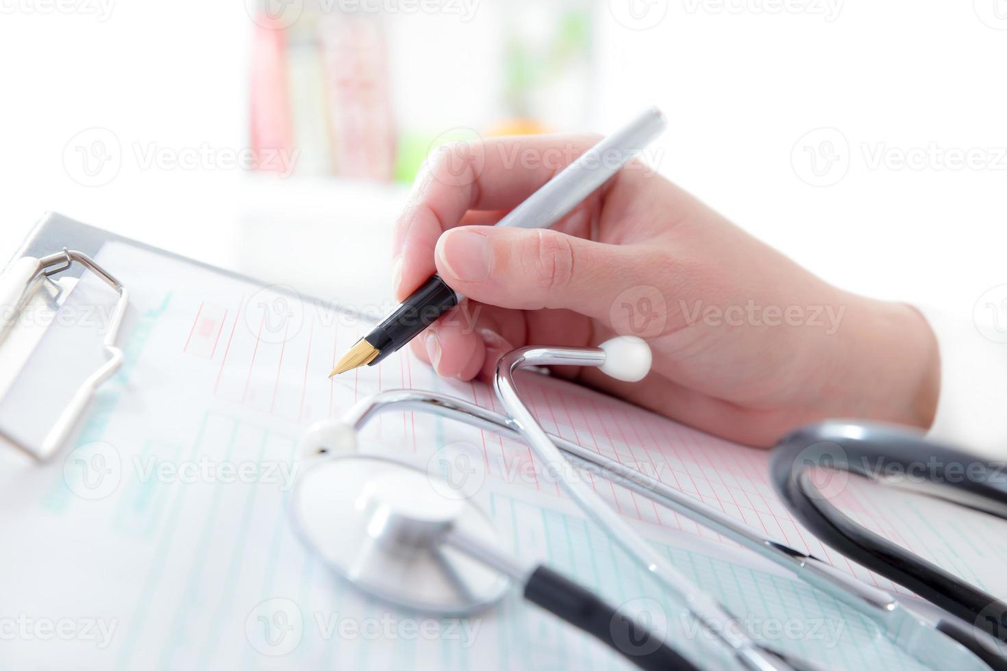 medico che scrive una prescrizione su esame medico foto