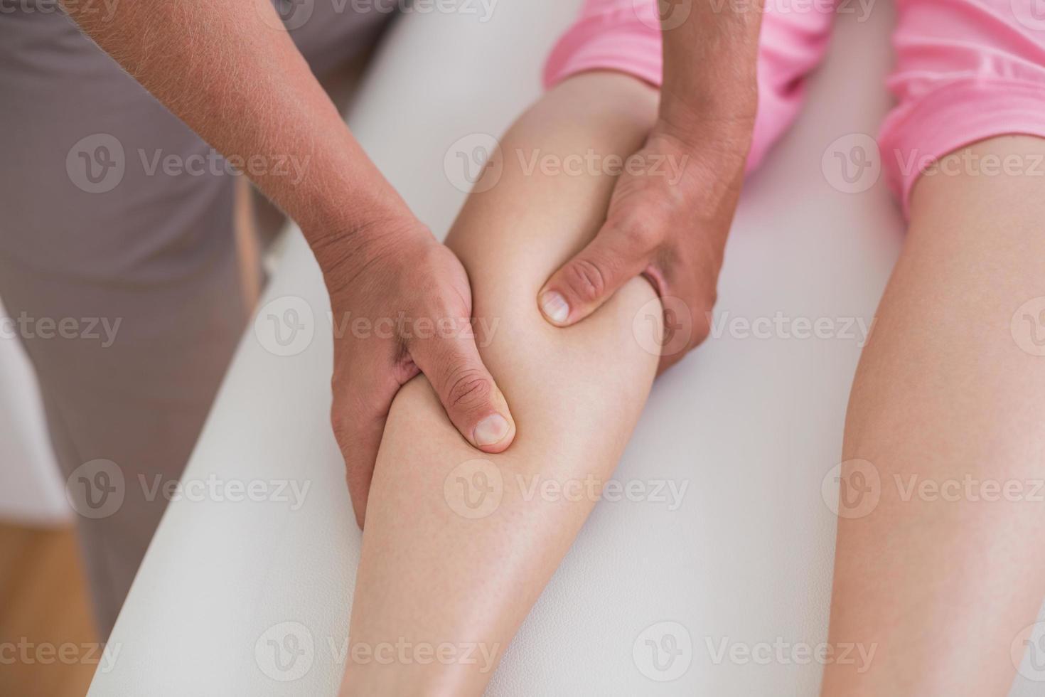 Fisioterapista che fa massaggio al polpaccio foto